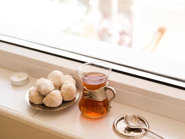 Pasteles, té y cuchara delante de la disposición de la ventana