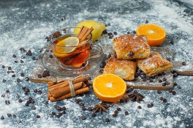 Pasteles con té, harina, chips de choco, especias, naranja, limón, vista de ángulo alto en concreto y tabla de cortar