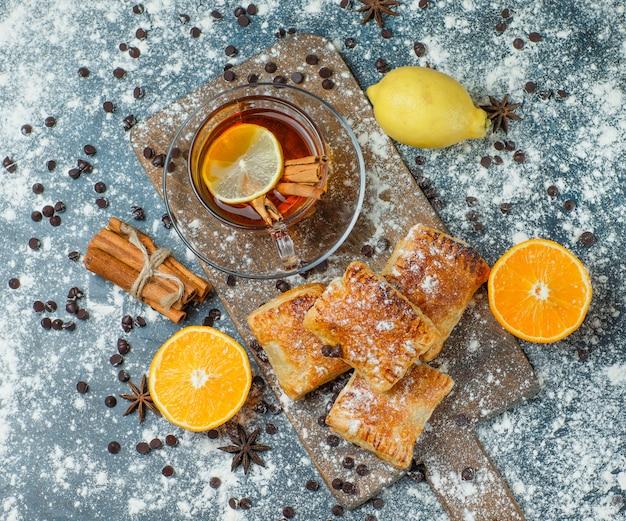 Pasteles con té, harina, chips de chocolate, especias, naranja, limón sobre hormigón y tabla de cortar