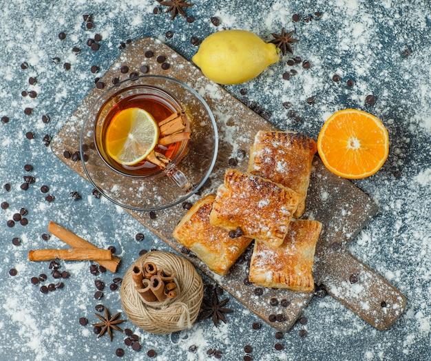 Pasteles con té, harina, choco chips, hilo, especias, naranja, limón sobre hormigón y tabla de cortar