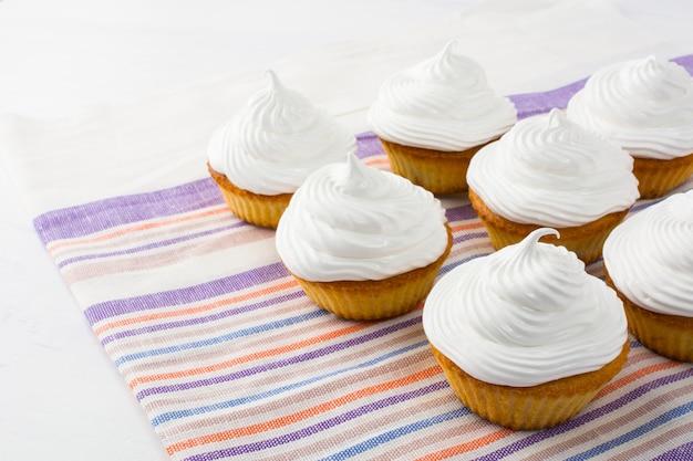 Pastelitos blancos de cumpleaños en la servilleta de lino a rayas