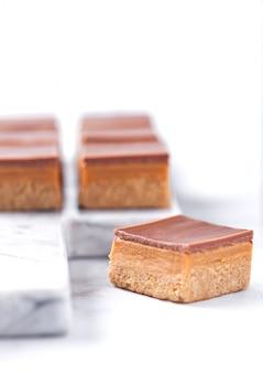 Pastelitos de tarta de caramelo y galleta postre sobre tabla de mármol