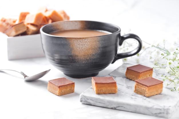 Pastelitos de tarta de caramelo y galletas postre sobre tabla de mármol y taza de capuchino