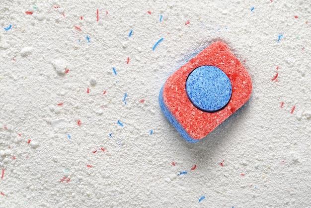 Pastilla de detergente para lavavajillas de color rojo y azul en polvo. concepto de elección. copia espacio