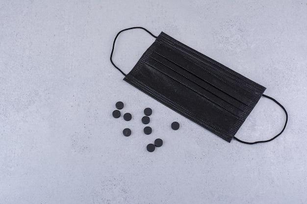 Pastilla negra y mascarilla médica sobre superficie de mármol. foto de alta calidad
