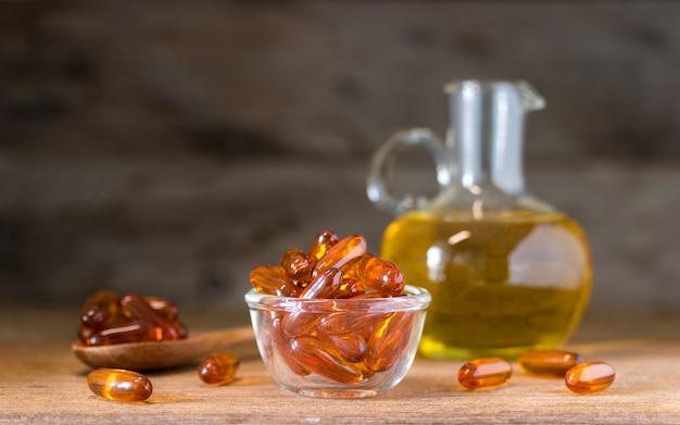 Pastillas de aceite de pescado en un recipiente de vidrio sobre mesa de madera