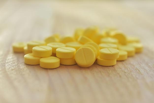 Pastillas amarillas en mesa de madera