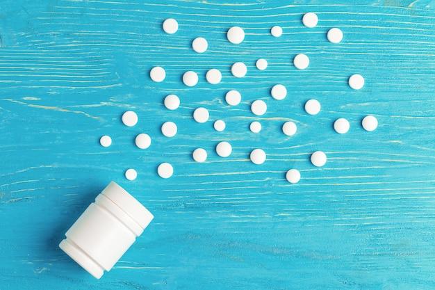 Pastillas blancas derramadas de un recipiente blanco sobre una mesa de madera azul