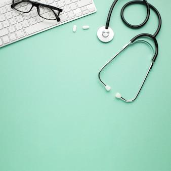 Pastillas blancas y estetoscopio cerca de gafas en el teclado inalámbrico sobre fondo