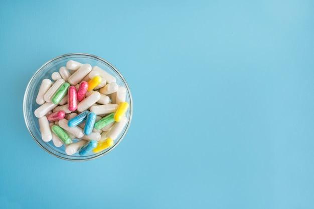 Pastillas de colores y medicamentos en placa de vidrio