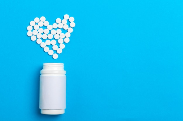 Pastillas corazón de frasco de pastillas sobre fondo azul, vista superior