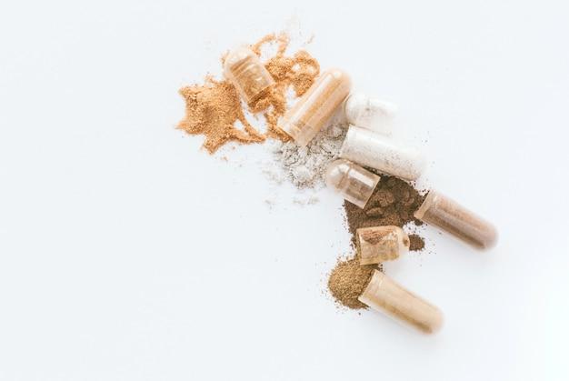 Pastillas de hierbas. abra las cápsulas y el polvo herbarios en el fondo blanco. copyspace