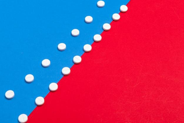 Pastillas médicas blancas sobre un fondo rojo y azul bicolor