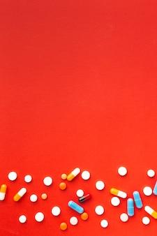 Pastillas médicas coloridas y fondo rojo del espacio de la copia