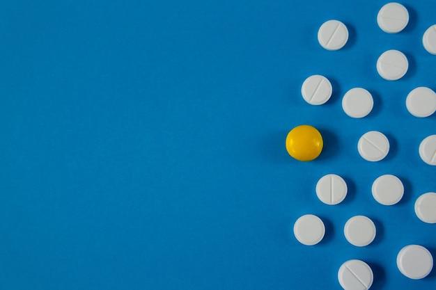 Pastillas de medicina y salud sobre fondo azul desde arriba