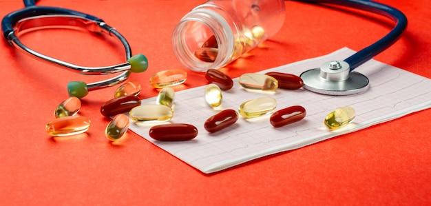 Pastillas, vitaminas, estetoscopio, cardiograma, en la mesa. pared naranja. de cerca.