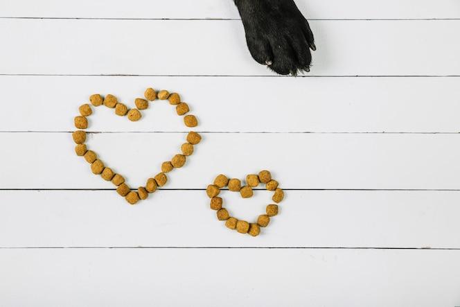 Pata de perro cerca de corazones de comida