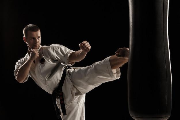 Patada redonda de karate en un saco de boxeo