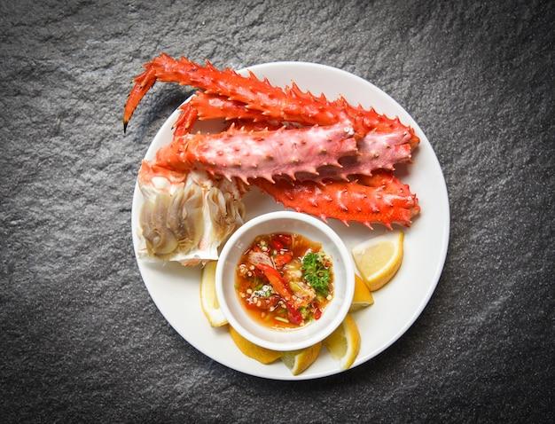 Patas de cangrejo real de alaska cocinan mariscos con salsa de limón en un plato blanco