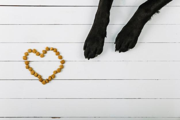 Las patas de perro cerca del corazón de la comida