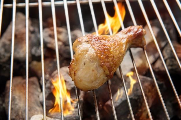 Patas de pollo asadas sobre las llamas en una barbacoa.