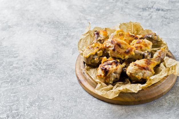Patas de pollo a la barbacoa en la bandeja con el papel kraft.