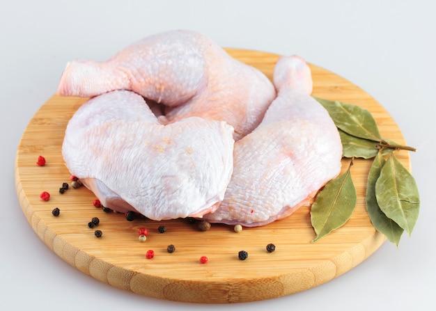 Patas de pollo crudo sobre un fondo blanco.