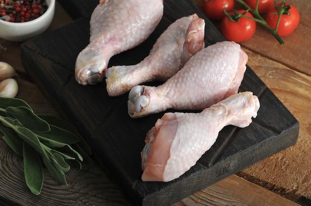 Patas de pollo crudo sobre una tabla de madera y una ramita de romero