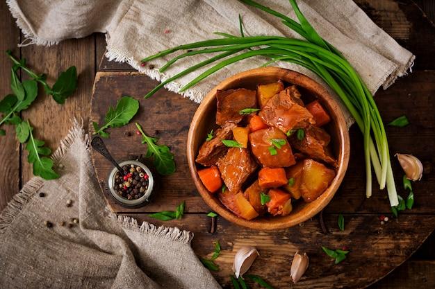 Patata al horno con carne bourguignon en la vieja mesa de madera en estilo rústico