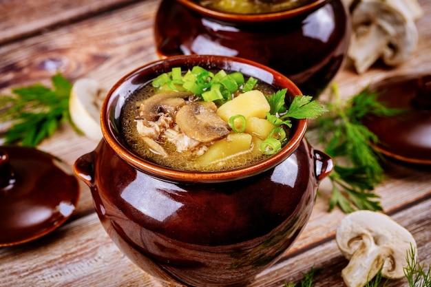 Patata con champiñones y carne guisada en una cazuela de barro con hierbas