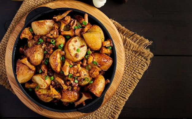 Patatas al horno con ajo, hierbas y rebozuelos fritos en una sartén de hierro fundido