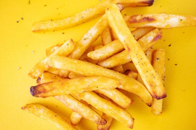 Patatas al horno con hierbas aromáticas sobre un fondo amarillo.