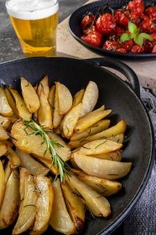 Patatas asadas con romero en cazuela de hierro y plato de tomates confitados sobre fondo oscuro.