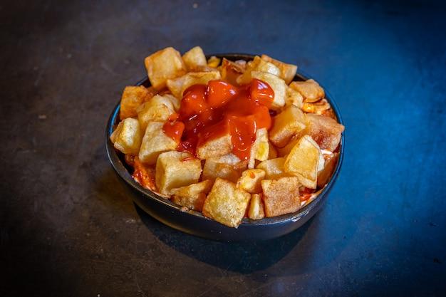 Patatas bravas con salsa de tomate ketchup sobre un fondo negro, sobre una placa azul