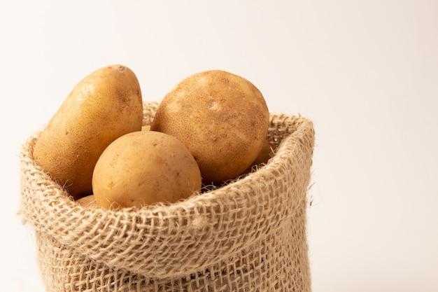 Patatas frescas y crudas en un saco rústico aislado en el fondo de color blanco.