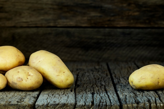 Patatas frescas en una vieja mesa de madera
