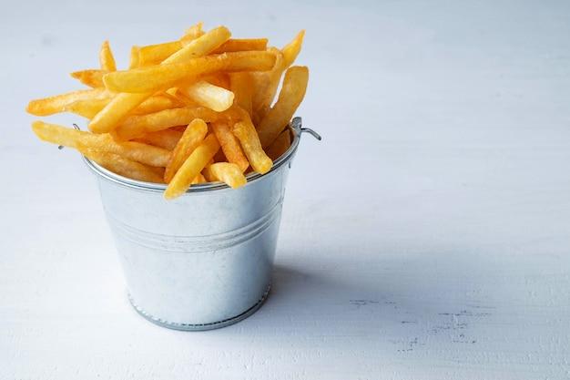 Patatas fritas frescas en la mesa de madera blanca