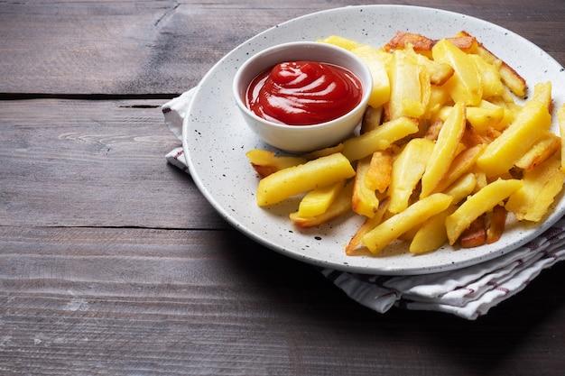 Patatas fritas fritas con salsa de tomate ketchup en un plato.