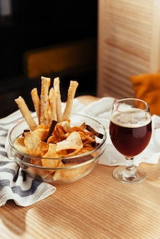 Patatas fritas y galletas saladas a la cerveza. menú publicitario de tiro