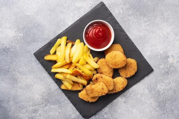 Patatas fritas y nuggets de pollo con salsa de tomate ketchup.