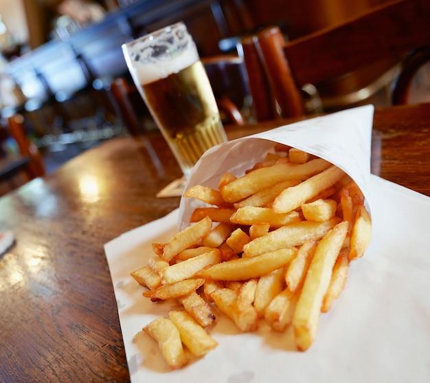 Patatas fritas en una pequeña bolsa de papel blanco sobre una mesa de madera en un pub de bruselas