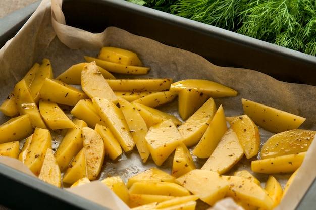 Patatas fritas rebanadas en papel de hornear y eneldo verde