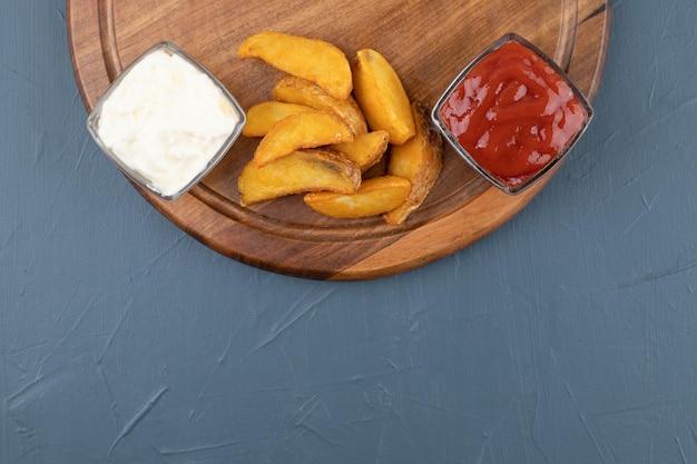 Patatas fritas con tazones de ketchup y mayonesa sobre tabla de madera en fondo azul. foto de alta calidad