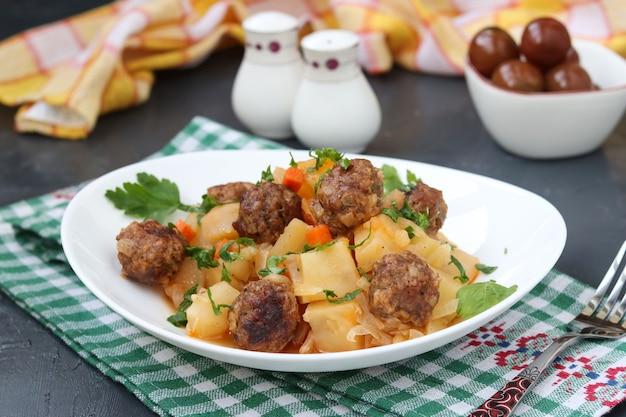 Patatas guisadas con albóndigas en un plato blanco sobre la oscuridad