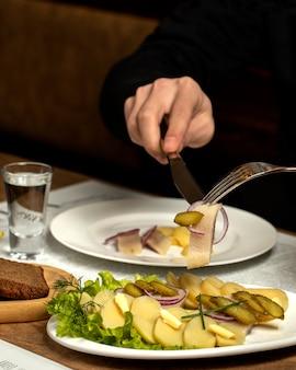 Patatas hervidas y arenque con cebolla