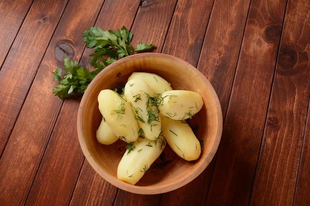 Patatas hervidas en un recipiente de madera con hierbas. estilo rústico