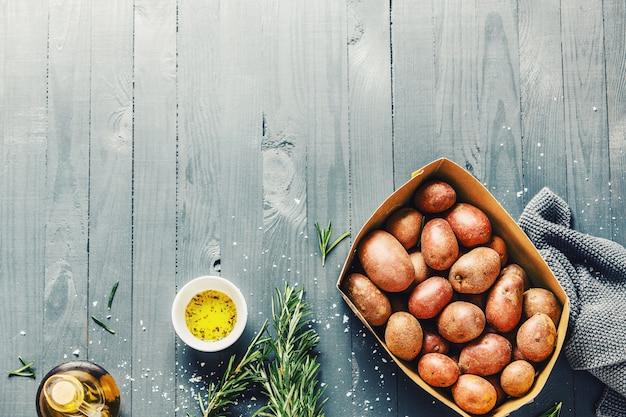Patatas orgánicas crudas con especias en mesa de madera copyspace