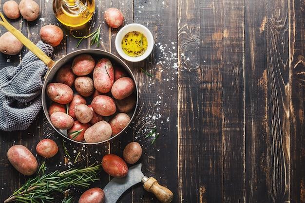 Patatas orgánicas crudas con especias en mesa de madera