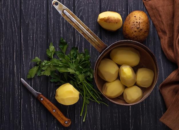 Patatas peladas sin cocer sobre fondo oscuro