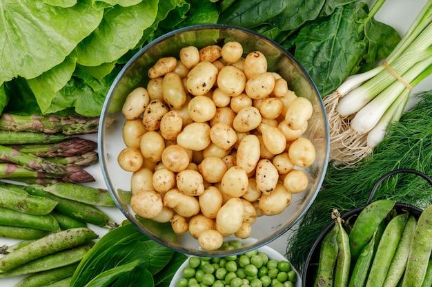 Patatas en un recipiente de vidrio con guisantes verdes, vainas, espinacas, eneldo, lechuga, espárragos, cebolla verde vista superior en la pared blanca